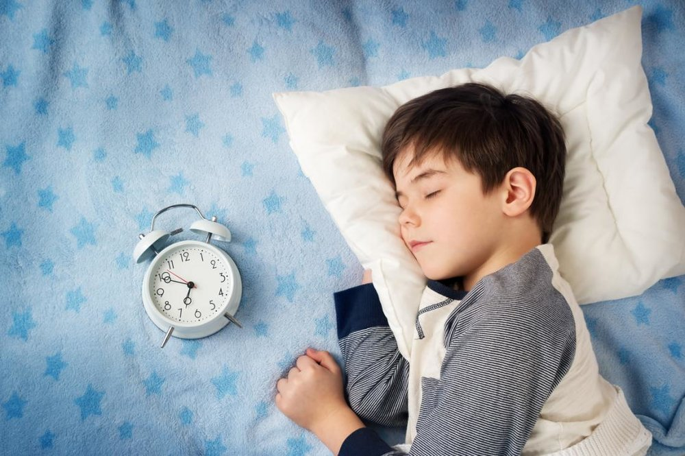 child-sleeping-with-clock.jpg
