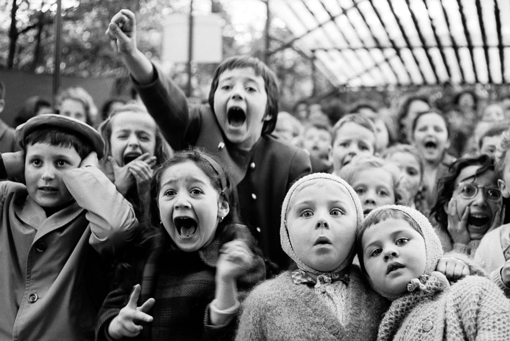 "Alfred Eisenstaedt, Children in Paris watching a ""St. George and the Dragon"" puppet show, 1963."