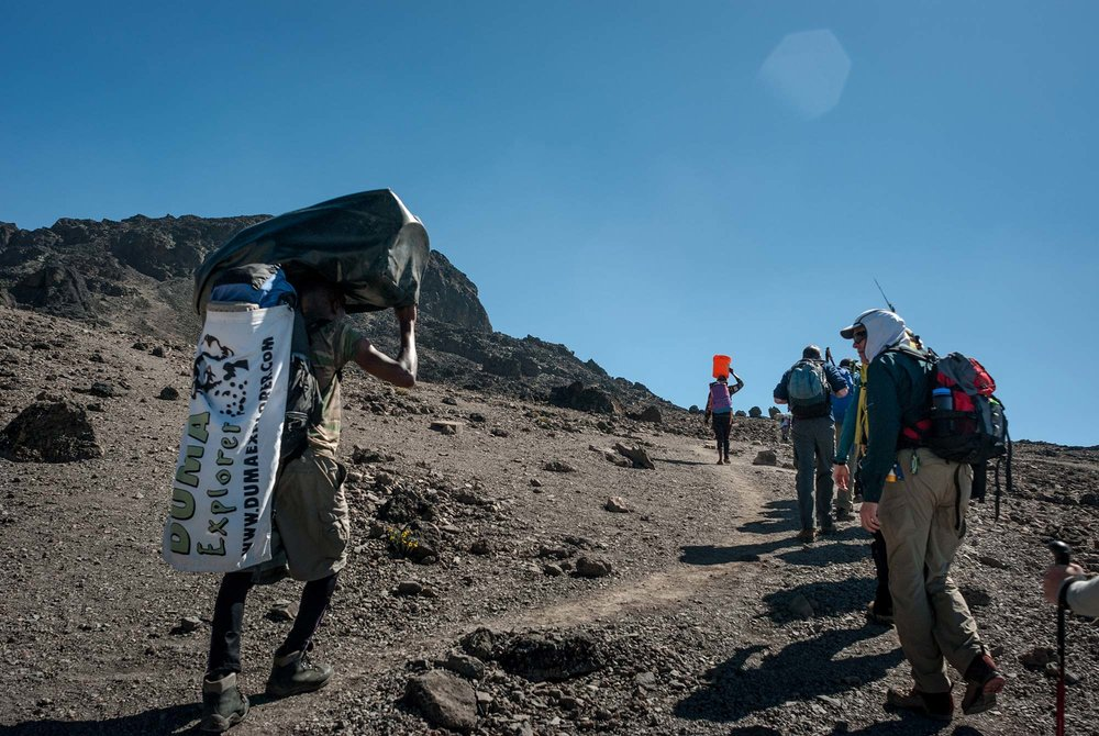 D6-28-dickson-carries-the-team-flag-karanga-to-barufu-camp-kilimanjaro.jpg
