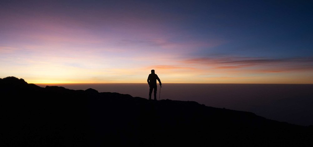 A Kilimanjaro climber near the summit looks out at the clouds 10,000 feet below at dawn.