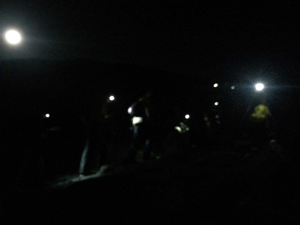 Blur of headlights as Kilimanjaro hikers depart camp for summit.