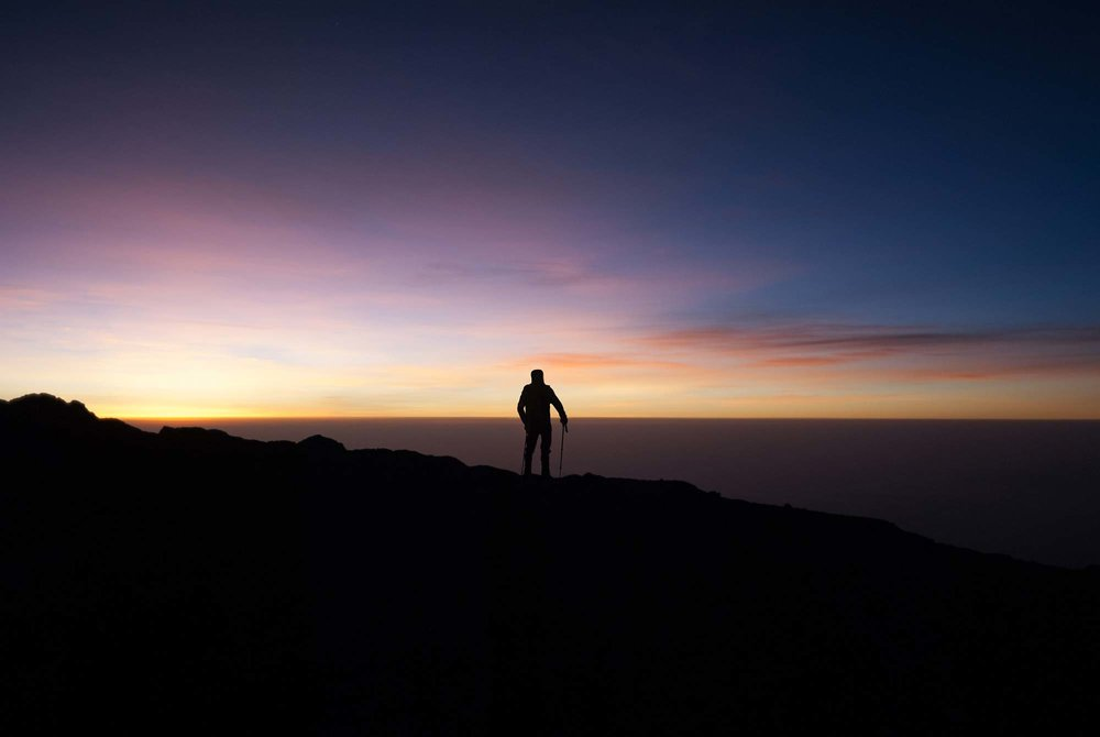 A Kilimanjaro climber looking South East from the crater rim out over the clouds 10,000 feet below as the sun began to peak over the horizon.