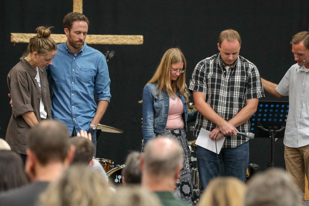Reuben Munn praying with the Church Northwest team last Sunday.