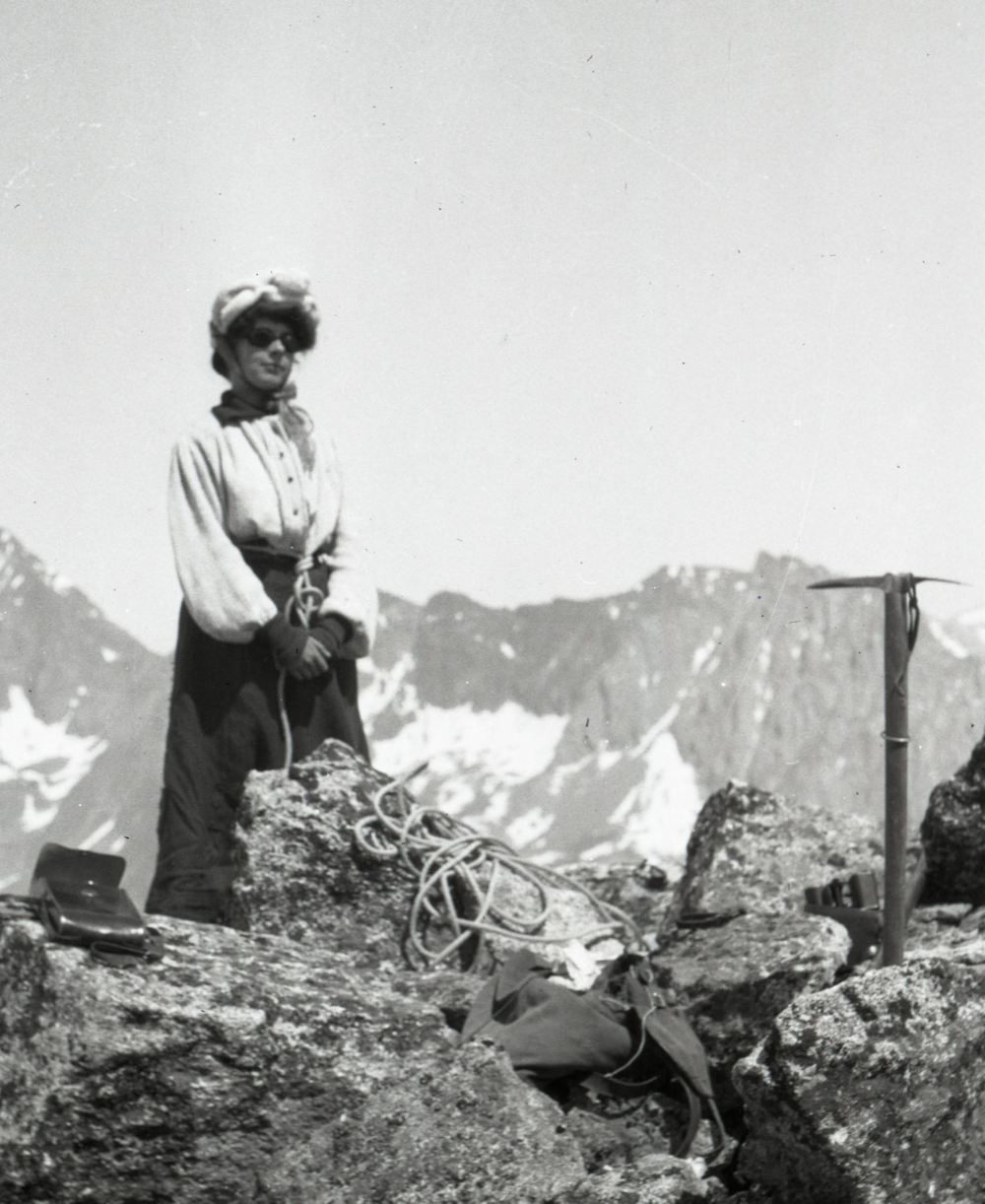 Photo credit: American Alpine Club Library.  From our Andrew J. Gilmour collection, taken in the Alps around 1910. A woman in a long coat and glacier goggles stands in front of a narrow rock prominence. She is holding an ice axe and is part of a rope team, roped to other mountaineers.