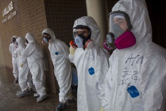 The Mark News: Workers dressed in protective suits and masks wait outside a building at J-Village, a soccer training complex now serving as an operation base for those battling Japan's nuclear disaster, in Japan's Fukushima prefecture, Friday, Nov. 11, 2011. (AP Photo/David Guttenfelder, Pool)