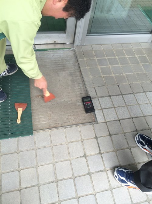 Taking dust samples underneath floor matts at a convenience store Proves radiation is being spread everywhere