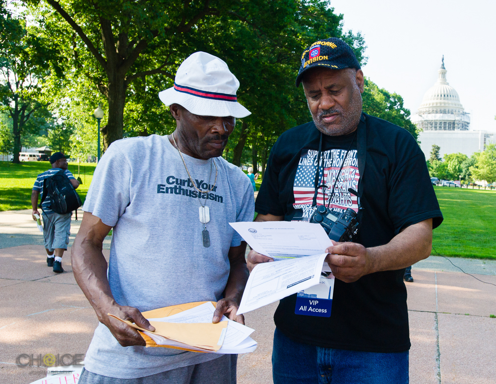 "Stanley Coward, 58, left, who served in U.S. Army from 1978-2014 gets assistance from Curtis Holt, right, U.S. Army 1979-1992, a volunteer with Disabled American Veterans (DAV). Curtis, himself a service-disabled veteran, helps other veterans navigate the complexities of applying for VA benefits. America's Vets Helping Vets For Life ""March 4 Veterans Rights."" Rally, May 28, 2016 Washington, D.C.(Rodney Choice/Choice Photography/www.choicephotography.com)"