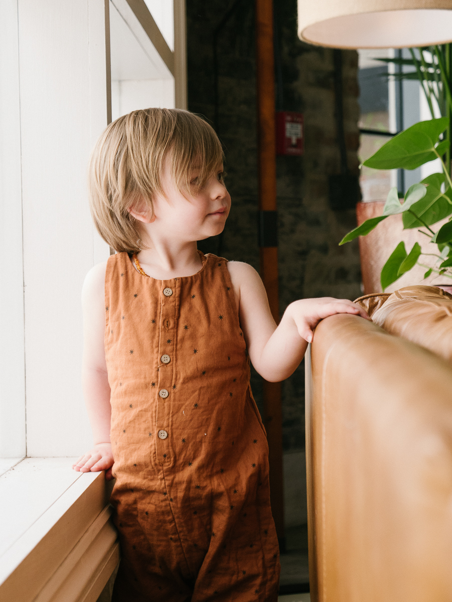 toddley boy in brown romper