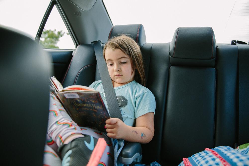 girl reading in back of car