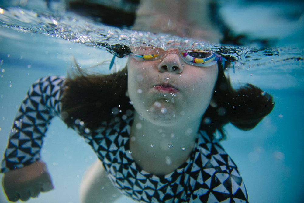 girl swimming underwater bubbles