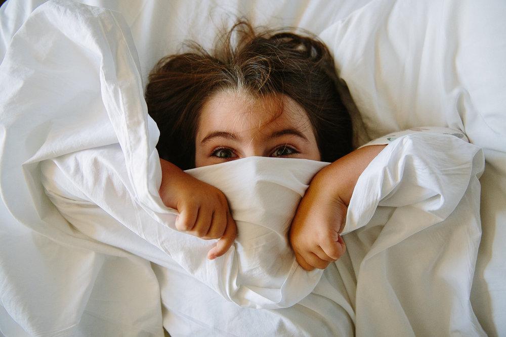 kid hiding face bed