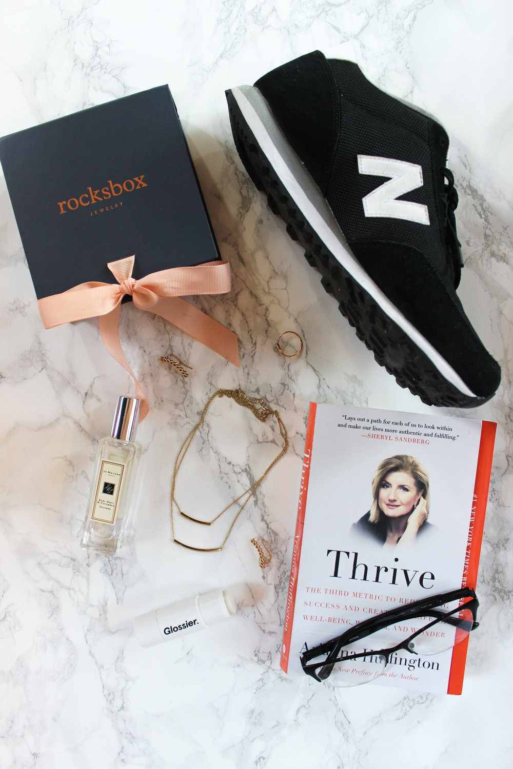 New Balance 501 black sneakers, rocksbox, thrive by arianna huffington, jo malone cologne in earl grey and cucumber, glossier haloscope in moonstone