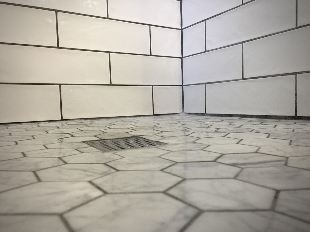 The marble hexagon tile flows from the shower onto the floor of the bathroom.