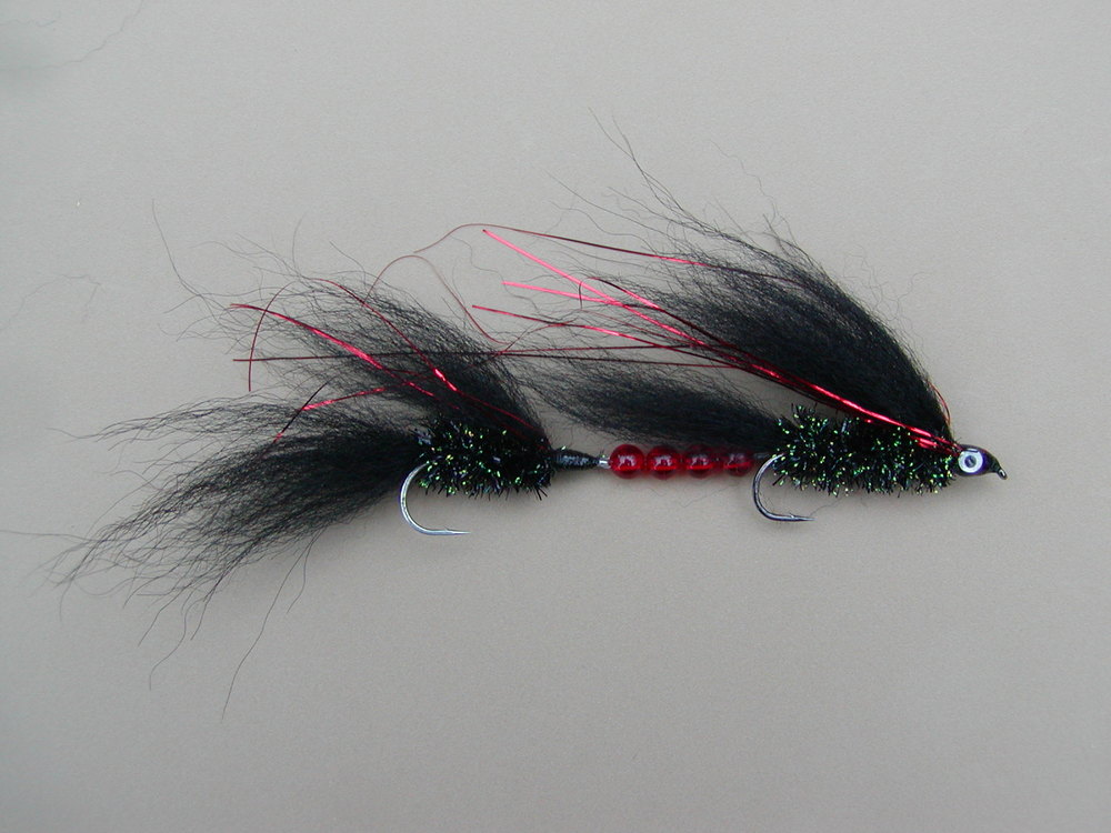 "Black & Red Tandem Trolling Fly #2   The Black & Red Wooly Worm has been the #1 choice of fly casters fishing at Pyramid Lake Nevada for more than 4 decades.  I have designed a tandem Arctic Fox fur trolling fly in this color specifically for use at Pyramid Lake NV.  I fished it for the first time late December 2015.  On dark over cast days it was our best producer when trolled near the surface on sinking fly lines.  I recommend black flies when fishing in low light conditions because it gives the best contrast.  By definition ""Low Light Conditions"" do not have the light to reflect off flashy materials.  I would confidently troll this fly on any lake, not just Pyramid."