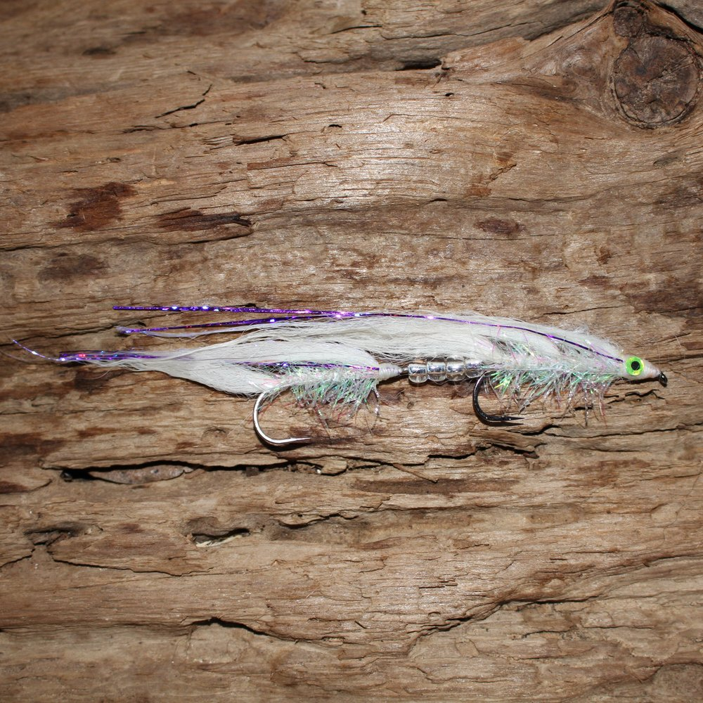 "UV WHITE, Tandem Arctic Fox Trolling Fly   This fly was originally tied on request for an angler from Pennsylvania headed to 31 Mile Lake in northern Canada. The target fish was mackinaw that feed on ""white fish"". He was so successful trolling deep for the macs that he has been reordering. This pattern has been effective on mackinaw at Flaming Gorge WY. Anglers wanting an even longer fly will put a UV White tube fly or two in line ahead of the fly. Mountain Whitefish are on the mackinaw diet in Lake Tahoe CA and other cold water fisheries.  This fly is similar to my other UV Pond Smelt patterns. It is tied with white fox fur with a few strands of holographic purple mylar. The fly really lights up in the water with an overlay of UV Angel Hair that is noticeable in the photo. Another feature of a white fly is that you can custom color it with felt tip pens."