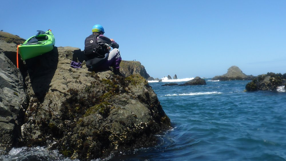 Liquid Fusion Kayaking's Cate Hawthorne hops out of her kayak to climb on the rocks to shoot video for Liquid Fusion Kayaking's new Mendocino kayak videos.  Photo by Jeff Laxier