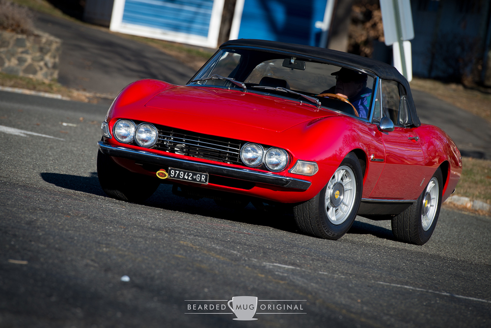 A Fiat Dino enters the parking lot of the local Cars and Croissants.