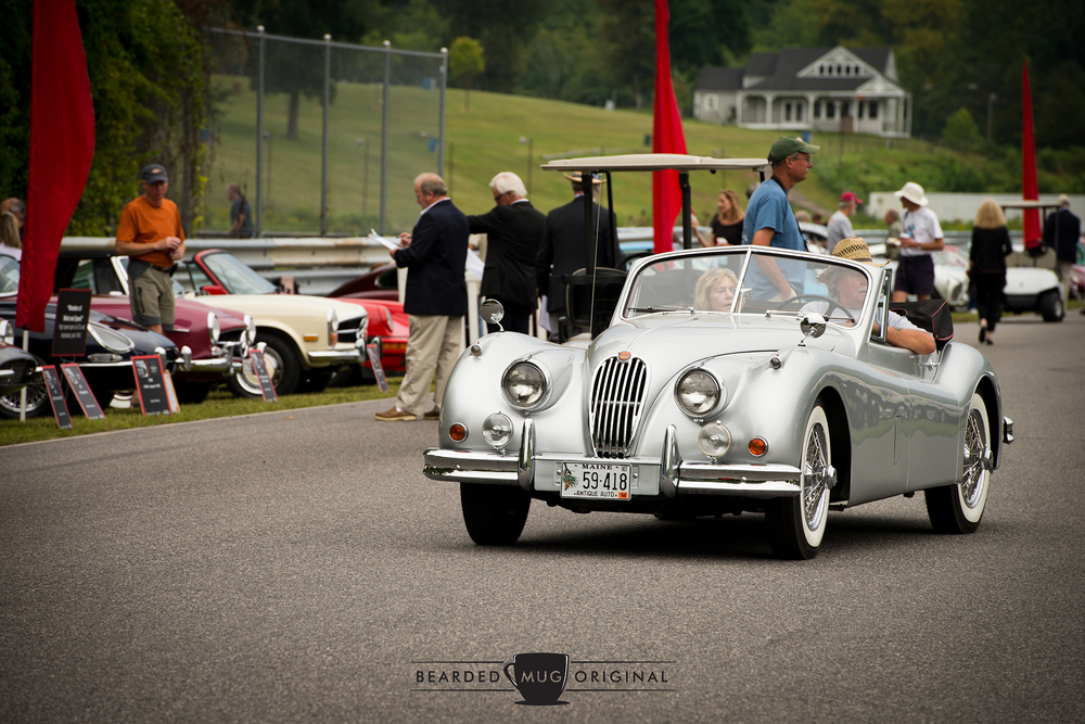A beautiful Jaguar XK140 Drophead Coupe scans for parking in its appropriate class.