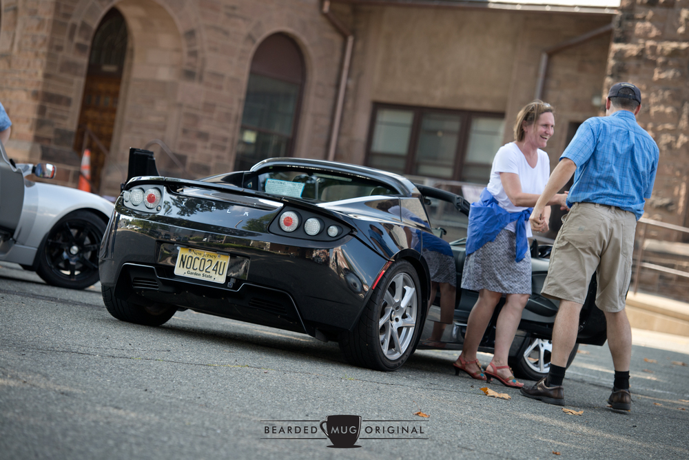 Sarah Stanley is helped out of the Tesla Roadster by its owner, Ian Giblin, after an exhilarating ride through Morristown.
