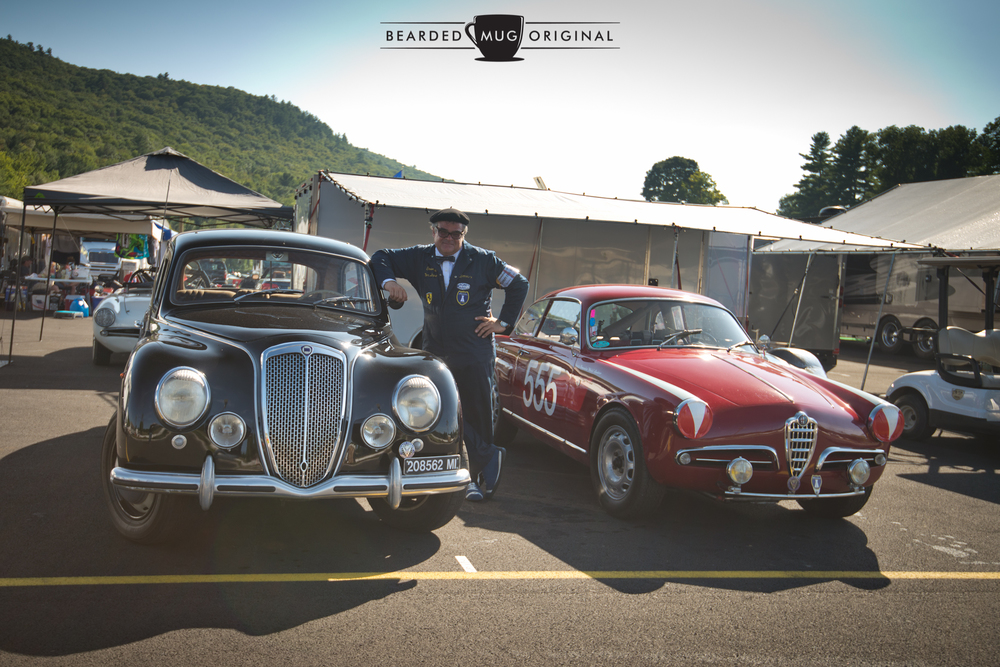 Santo, dressed in his father's period-correct garb, stands proudly between his 1953 Lancia Aurelia B10S and the featured Alfa.