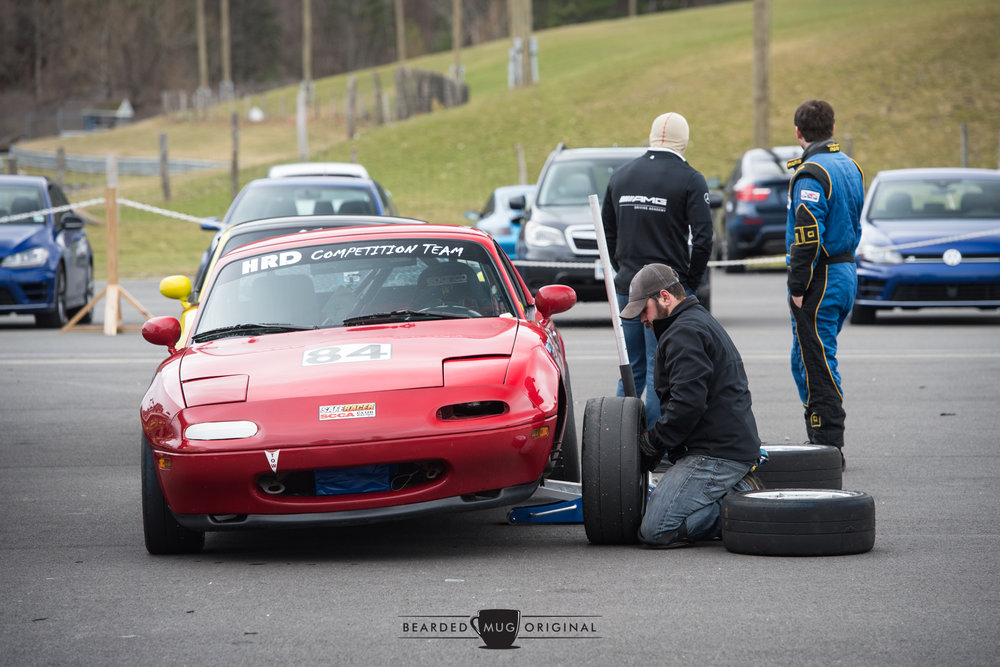 Race-prepped Miata gets some attention in A Paddock, while instructor and driver admire the coalition of Rs.