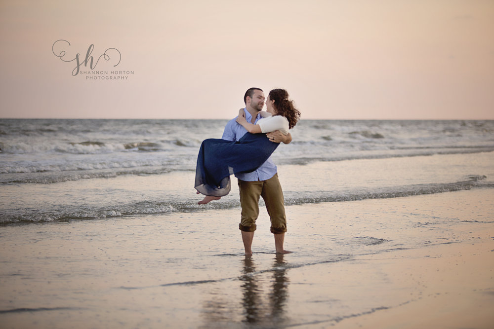 man-holding-pregnant-wife-in-ocean