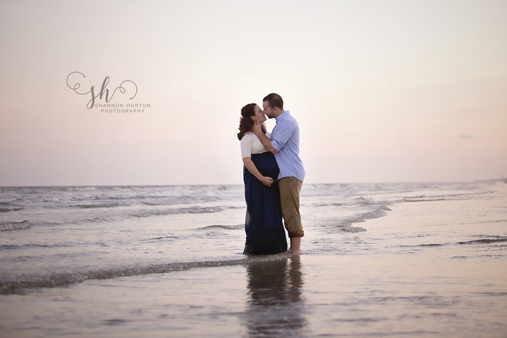 man-and-pregnant-wife-kissing-on-beach