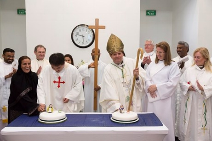 Her Excellency Sheikha Lubna bint Khalid bin Sultan Al Qasimi, the UAE Minister of State for Tolerance, cuts a cake with the Revd Hin Lai Ching, watched over by Bishop Michael Lewis and the Revd Charlotte Lloyd-Evans, and other clergy. (Photo: Diocese of Cyprus and the Gulf)