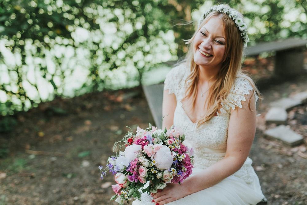Lachende Braut im Vintagestil mit einem großen Brautstrauß aus Wildblumen