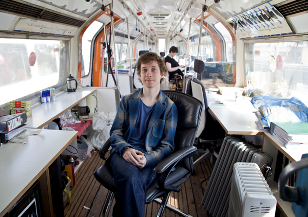 Auro Foxcroft, owner of Village Underground, sitting in one of the venue's train carriage start-up spaces.