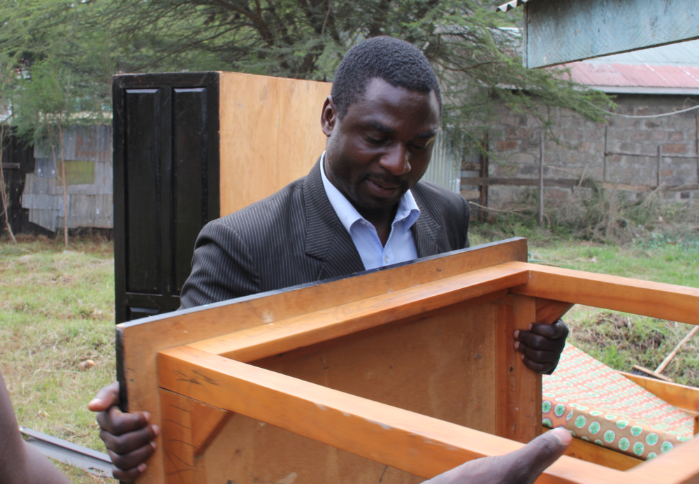 Pastor Shigonde moving furniture and leading the development of the land