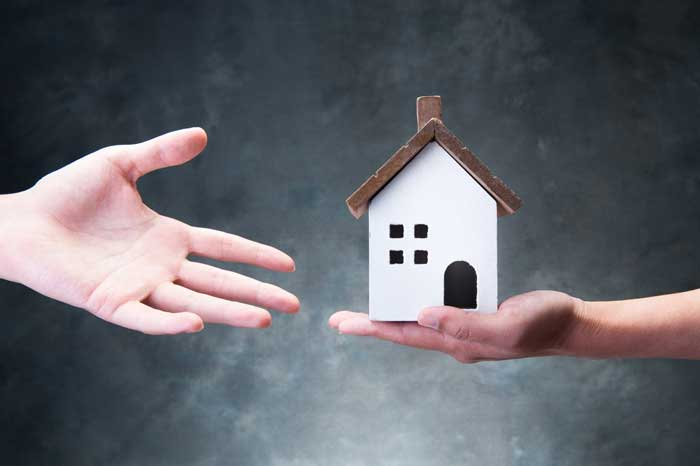 A hand passing over a wooden house, indicating inheritance