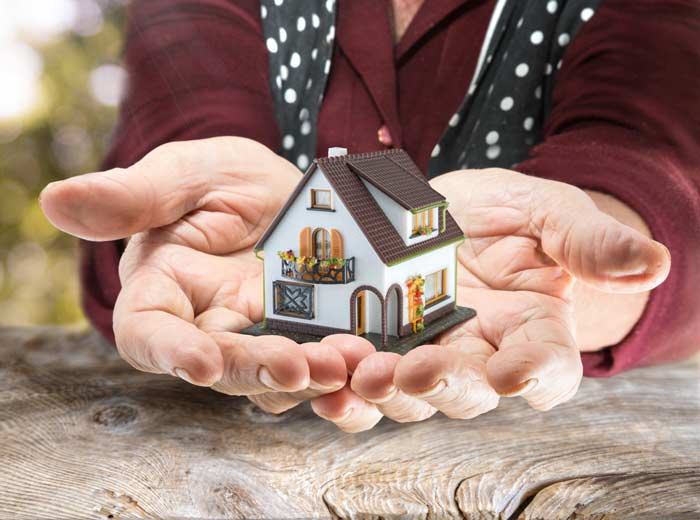 A pair of hands holding a small house, portraying inheritance