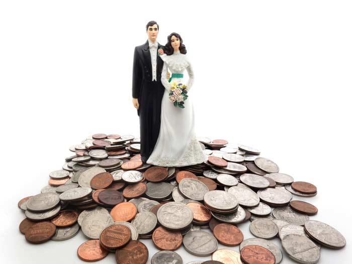 A wedding topper showing a married couple on top of coins