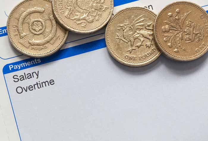 Several pound coins sat on a legal document
