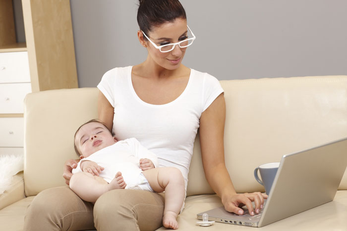 A businesswoman with a baby, checking emails whilst on maternity leave