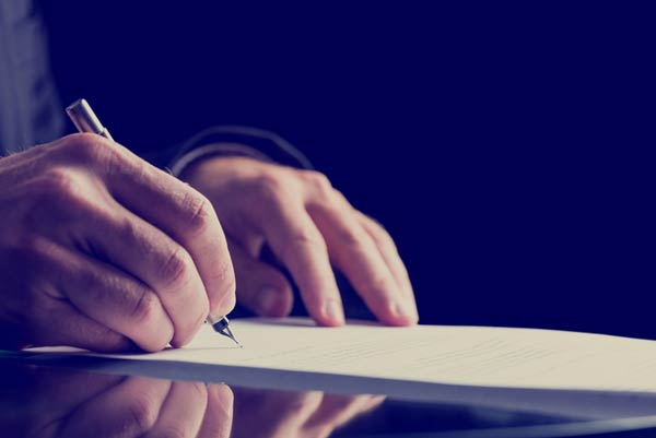 A pair of hands writing on a legal document