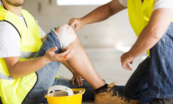 A construction worker cradling an injured knee