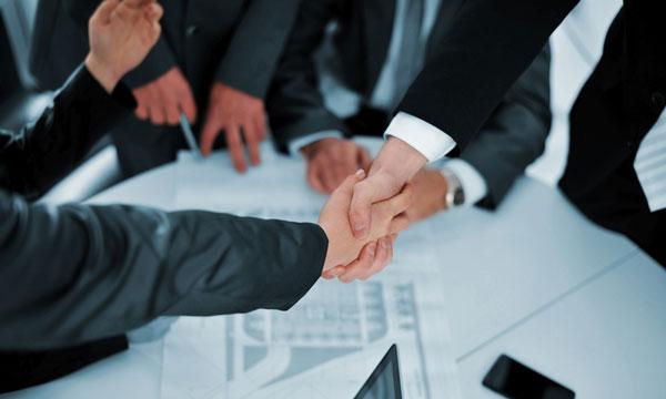 Businessmen shaking hands over legal agreements
