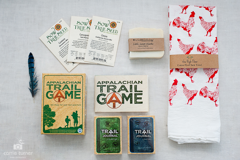 A collection of items for house and home: Sow True Seeds, Little Sweet Cheeks organic baby soap from A Wrinkle in Twine, a hand-printed Cotton Flour Sack Towel from the High Fiber, and the Appalachian Trail Game.