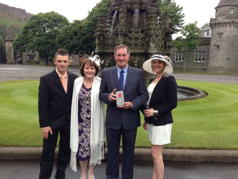 DOUGLAS COLLECTING HIS MBE MEDAL AT HOLYROOD PALACE WITH HIS WIFE - LIZ - AND CHILDREN - LINDA AND COLIN - IN JULY 2013