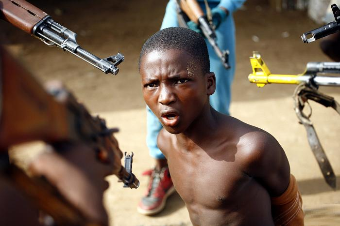 simply-war: A young man is held at gunpoint by child soldiers in Sierra Leone.