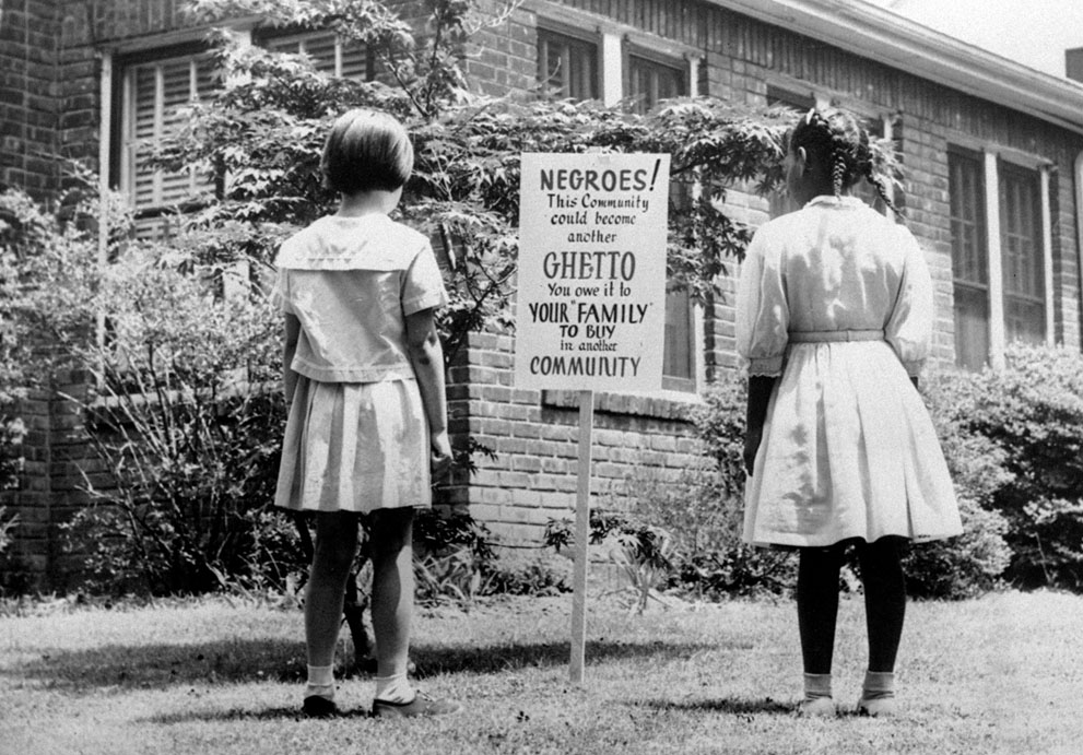 "super-international :      An African American and a white girl study a sign in the integrated Long Island community of Lakeview, New York, on April 1962. It reads ""Negroes! This community could become another ghetto. You owe it to your 'family' to buy in another community."" The sign was an attempt to keep African Americans from exceeding the number of whites who want to live in an integrated town."