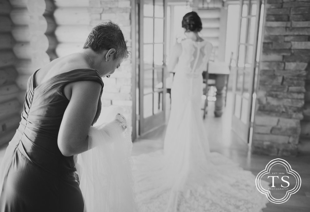 Mother crying seeing daughter in wedding gown
