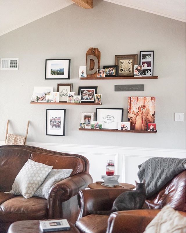 "I'm not sure if it's the pregnancy or me just being me...but this wall makes me so emo! It's exactly how I want my living room to feel—cozy with actual reminders of the blessings in our life (in photos, duh). 😍 ⠀⠀⠀⠀⠀⠀⠀⠀⠀ Jordan made these walnut shelves that I've had a vision for..for over a year. And when I told him last night that it was my favorite (late) Christmas present, he was quick to respond in typical Jordan fashion, ""Christmas? That's your early anniversary gift"".😉 ⠀⠀⠀⠀⠀⠀⠀⠀⠀ Our anny is June 1 😂 ⠀⠀⠀⠀⠀⠀⠀⠀⠀ But for real: my love language is PHOTOS 😭😭 I'll be sharing how and where I frame everyday + professional photos around my house to remind me of the little (big) things in life always. ❤️"