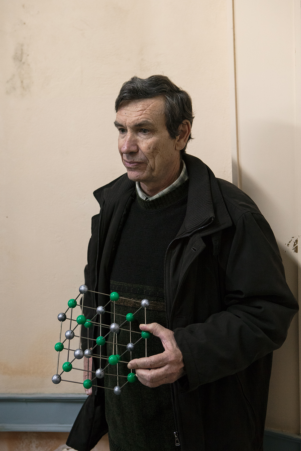Physics teacher holding a model of crystal salt. A large part of the school environment has been formed by people deeply devoted to their profession, almost like having a love affair with their job.