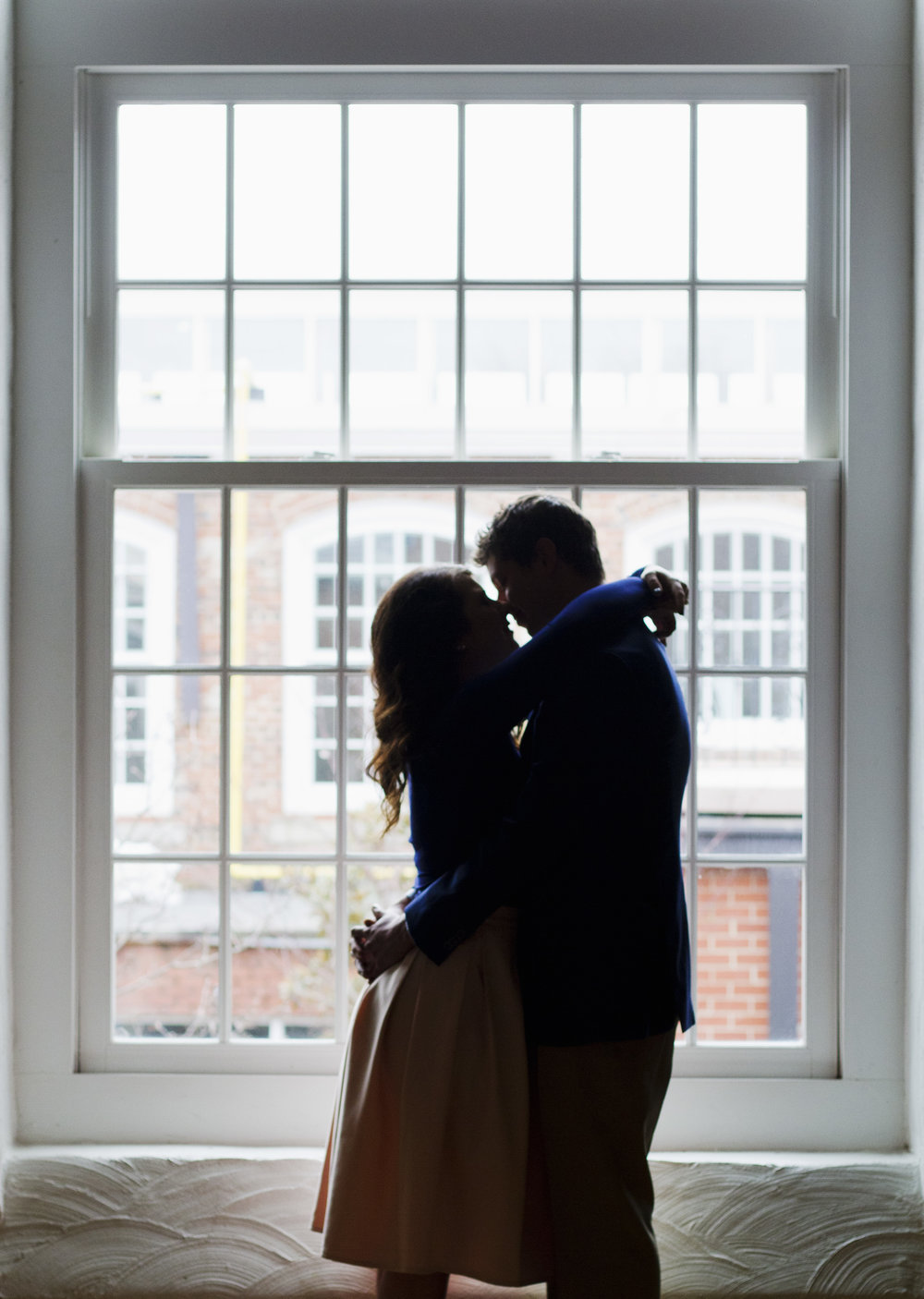 Romantic Engagement Photography at Revolution Mills Event Center Greensboro, NC in front of window. Winston Salem and Kernersville Wedding Photographer  Navy and pink color scheme coordination  Kissing sillhuette