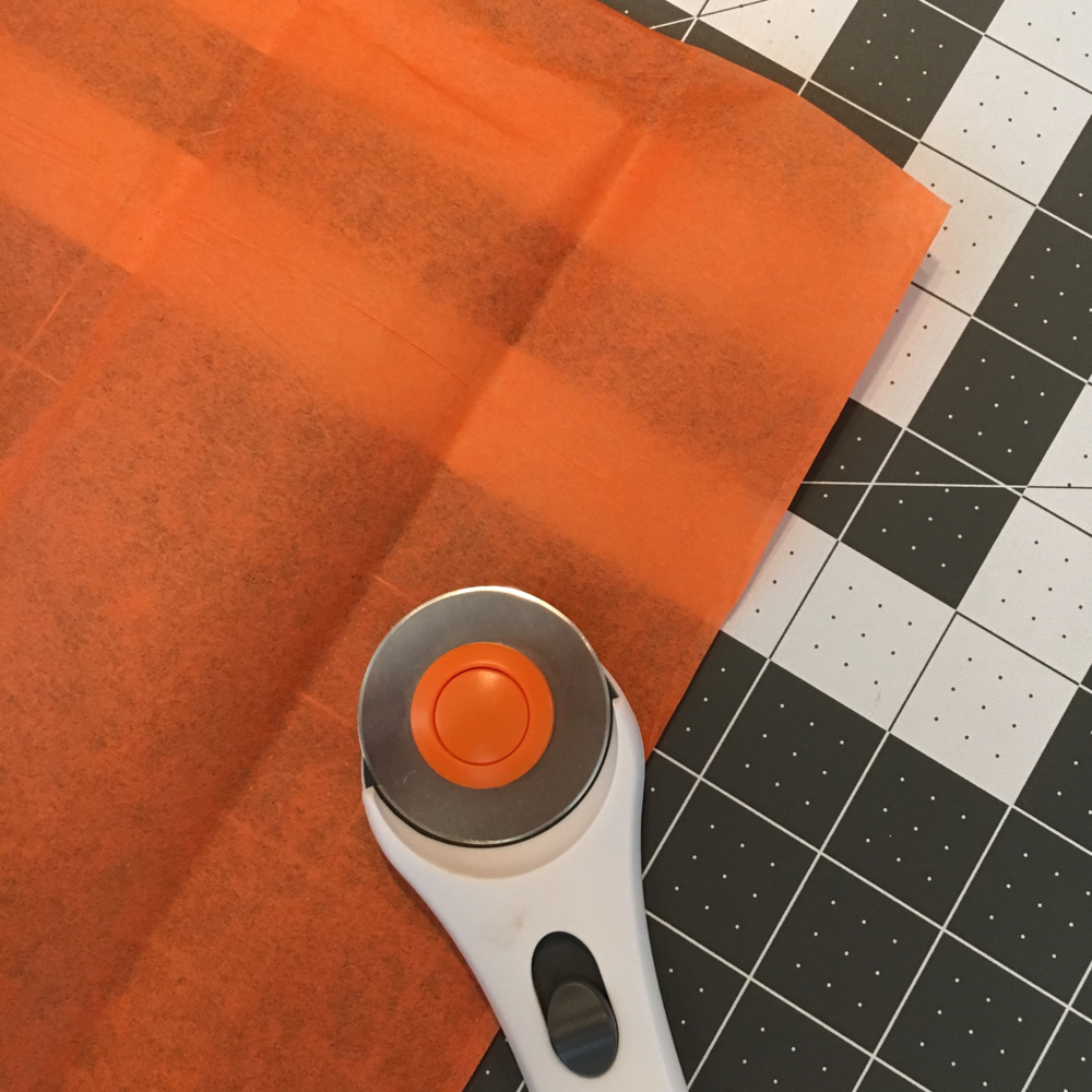 Use tissue paper and a rotary cutter + mat.