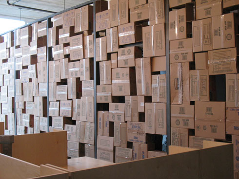 the randomly stacked boxes viewed from the desks