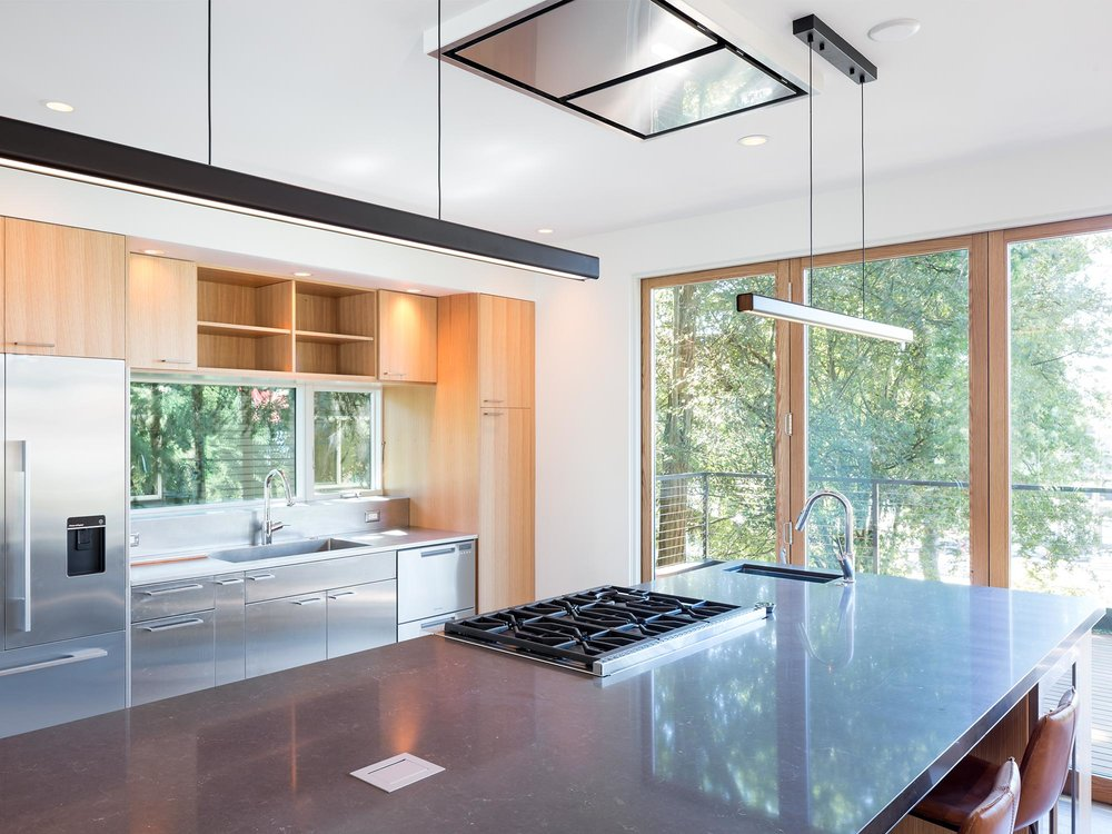 An expansive kitchen serves is the heart of the house for people who love to cook. A custom stainless steel sink & countertop unify the functional side of the kitchen below a large window.